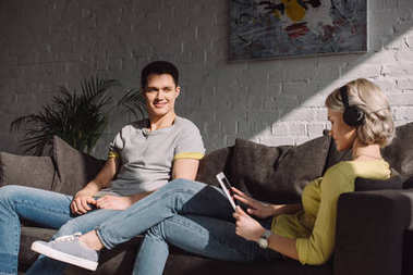 happy boyfriend looking at girlfriend with tablet at home