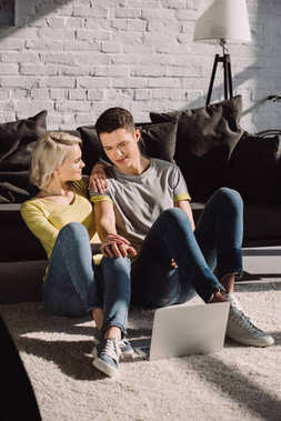 couple sitting on floor in living room with laptop