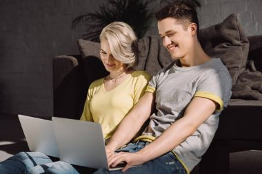 happy couple sitting on floor and using two laptops at home