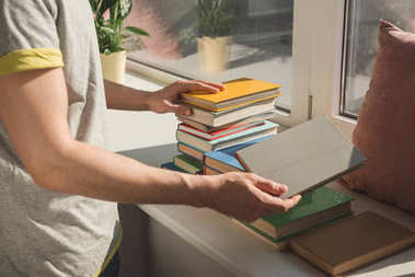 cropped image of man holding books at windowsill