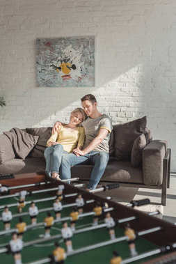 couple hugging and sitting on sofa in living room at home