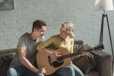 smiling girlfriend playing acoustic guitar for boyfriend at home