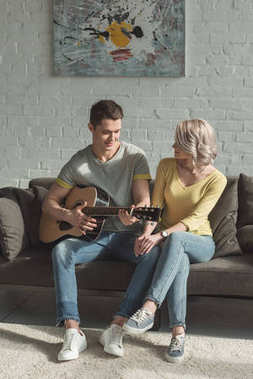 handsome boyfriend playing acoustic guitar for girlfriend at home