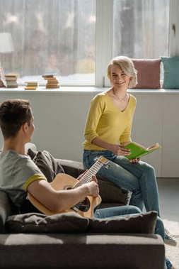 boyfriend holding acoustic guitar and girlfriend holding book on sofa