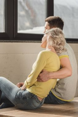 couple hugging and sitting on wooden floor at home