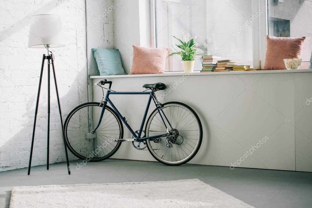 bicycle near windowsill in living room