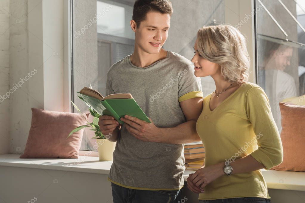 girlfriend looking into boyfriends book at home