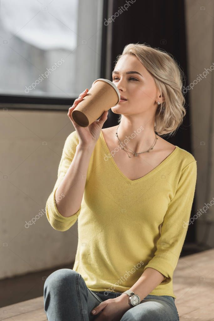 attractive girl drinking coffee from disposable coffee cup