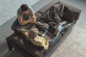 pohled z vysokého úhlu přítelkyně pomocí notebooku a přítel opírající se o pohovku doma