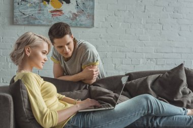 girlfriend using laptop and boyfriend looking at screen at home