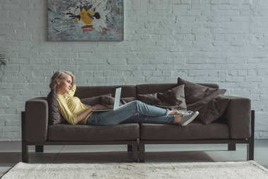 side view of beautiful girl lying with laptop on sofa