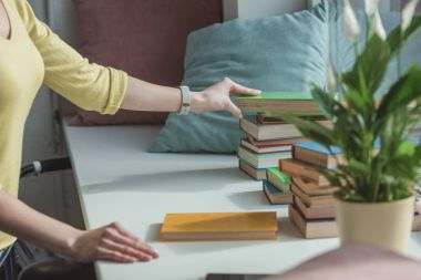 cropped image of woman taking book from stack on windowsill