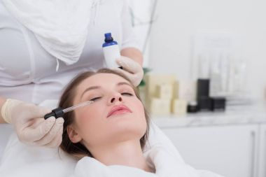 partial view of young woman receiving facial treatment made by cosmetologist in salon