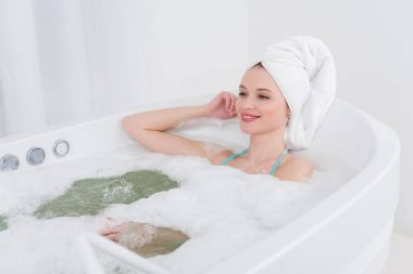 smiling woman with towel on head relaxing in bath with foam in spa salon