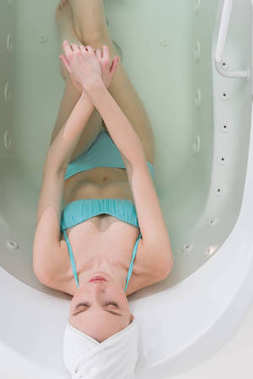 overhead view of young woman in swimming suit with towel on head relaxing in bath in spa salon