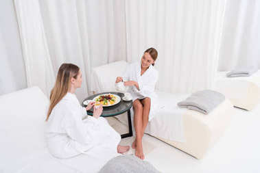 partial view of young women in white bathrobes drinking tea at table  in spa salon