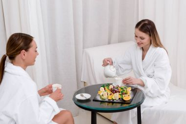young women in white bathrobes drinking tea at table in spa salon