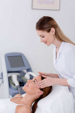 young woman getting head massage made by cosmetologist in salon
