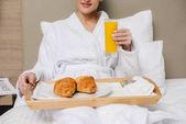 oříznutý snímek žena v županu relaxaci v hotelovém pokoji se snídaní v posteli