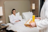 cropped shot of man carrying tray with tasty breakfast for girlfriend while she sitting in bed at hotel suite