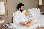 pohledný muž v županu s croissanty a šťávu na zásobník sedí na posteli v hotelu suite