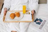 Photo cropped shot of man in bathrobe with food on tray sitting on bed at hotel suite