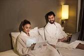 usmívající se pár v župany pomocí zařízení v posteli Suite hotel