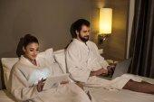 schönes Paar in Bademänteln mit Geräten im Bett der Hotelsuite