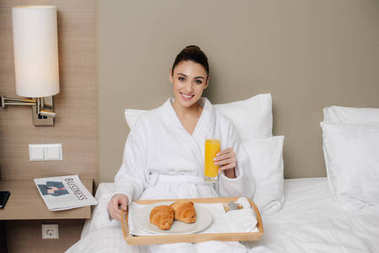 smiling woman in bathrobe relaxing at hotel room with breakfast in bed and looking at camera