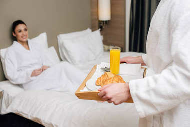Cropped shot of man carrying tray with breakfast for girlfriend while she sitting in bed at hotel suite stock vector