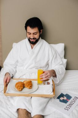 smiling man in bathrobe with food on tray sitting on bed at hotel suite
