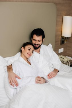 happy couple in bathrobes embracing in bed of hotel suite