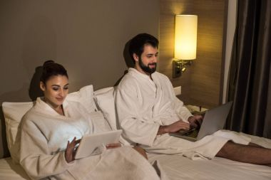 beautiful couple in bathrobes using devices in bed of hotel suite