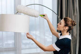 Fotografie young beautiful maid in uniform cleaning torchere with duster