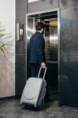 Fényképek üzletember-csomagokkal, belépő a hotelben lift