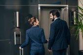 Fényképek a csomagokkal együtt lift várja üzleti emberek hátsó nézet