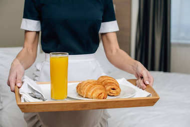 cropped shot of maid in uniform holding croissants and juice on tray at hotel suite