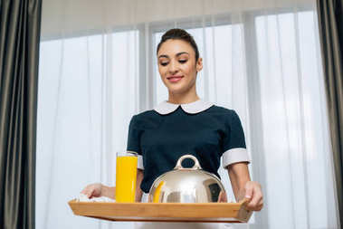 young smiling maid in uniform holding breakfast covered with cloche on tray