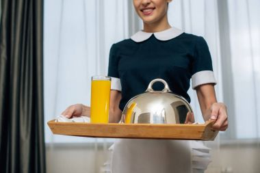 cropped shot of smiling maid in uniform holding breakfast covered with cloche on tray