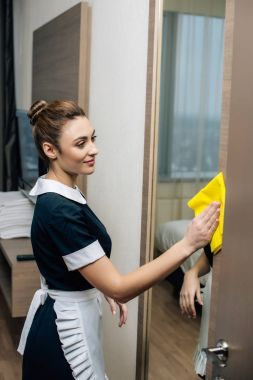 young smiling maid in uniform cleaning hotel suit with rag