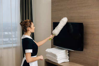 young beautiful maid in uniform cleaning hotel suit with duster