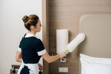 young attractive maid in uniform cleaning hotel suit with duster