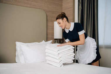 young smiling maid in uniform putting stack of clean towel on bed at hotel suit