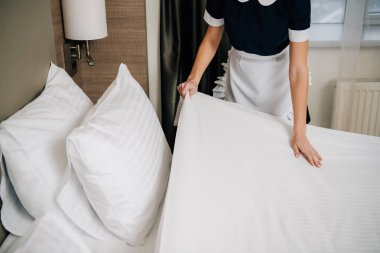 cropped shot of maid in uniform making bed at hotel suite