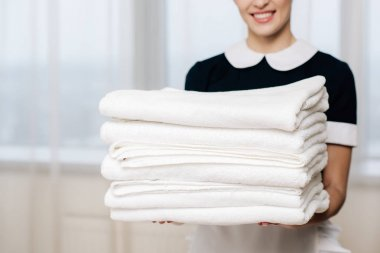 Cropped shot of smiling maid in uniform holding stack of clean towels stock vector