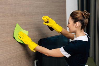 young beautiful maid in uniform wiping wood wall with rag and aerosol furniture cleaner