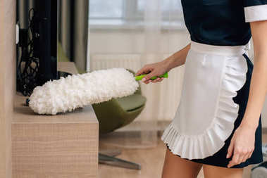 cropped shot of maid in uniform cleaning shelf with duster