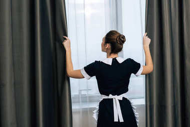 rear view of young beautiful maid in uniform shutting curtains