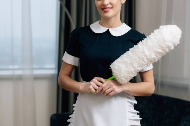 cropped shot of happy maid in uniform with duster