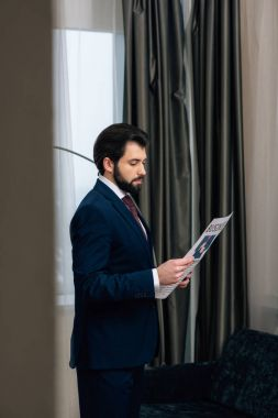 handsome businessman reading newspaper at hotel room